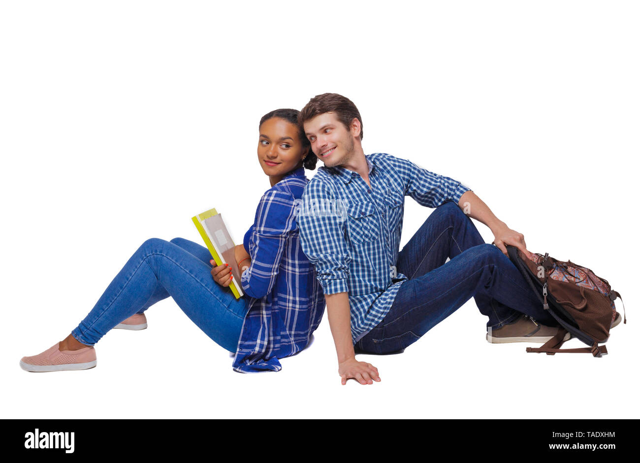 Side view of a couple of students who are sitting on the floor with their backs. Isolated over white background. Students are flirting sitting on the  Stock Photo