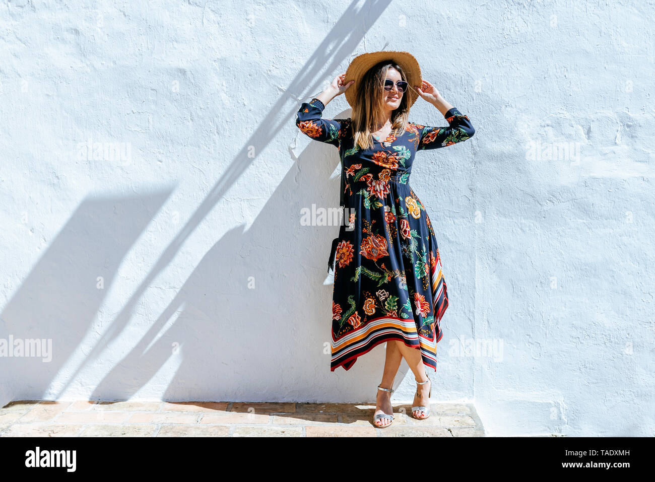 Spain, Cadiz, Vejer de la Frontera, fashionable woman with straw hat standing in front of white wall Stock Photo
