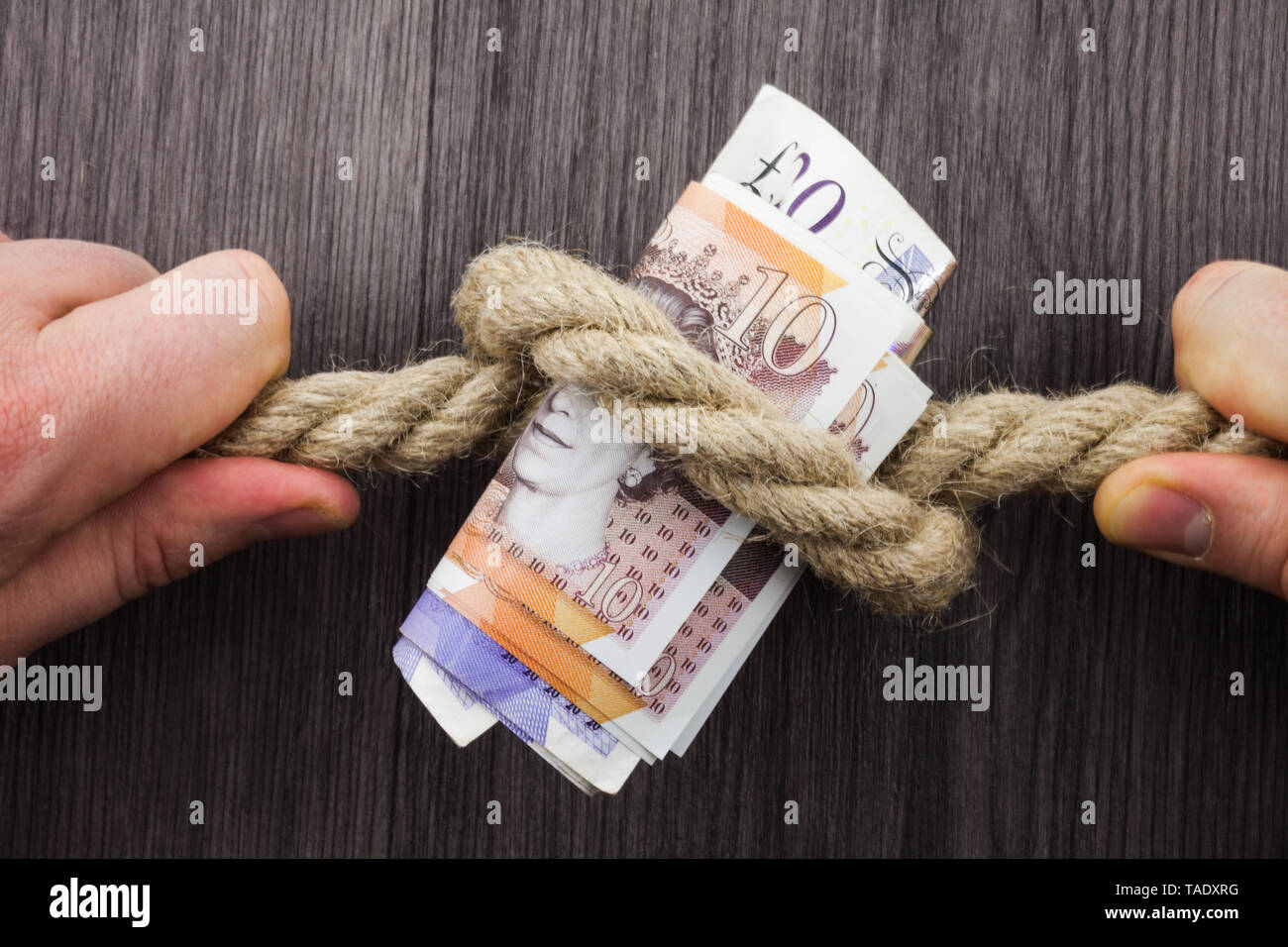 Front view wooden background two hands knot rope bills inside strong symbol - Stock Image