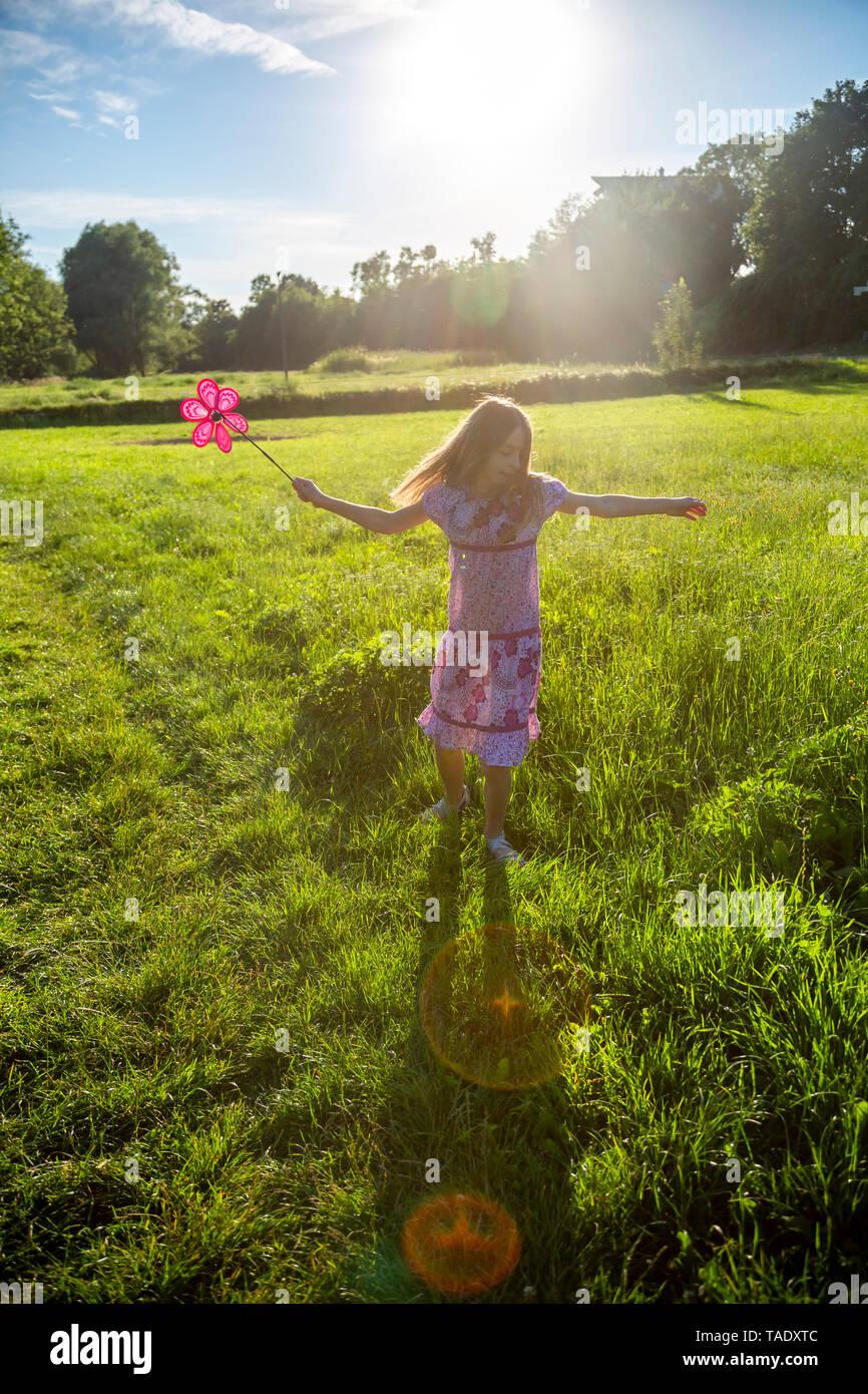 Happy girl with pinwheel running on summer meadow - Stock Image