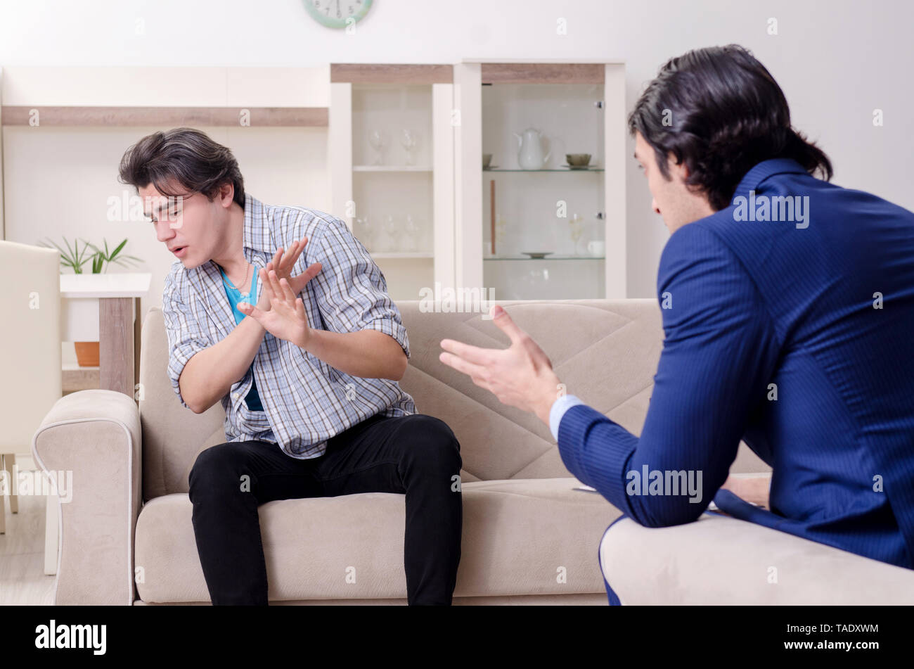 Young male patient discussing with psychologist personal problems - Stock Image