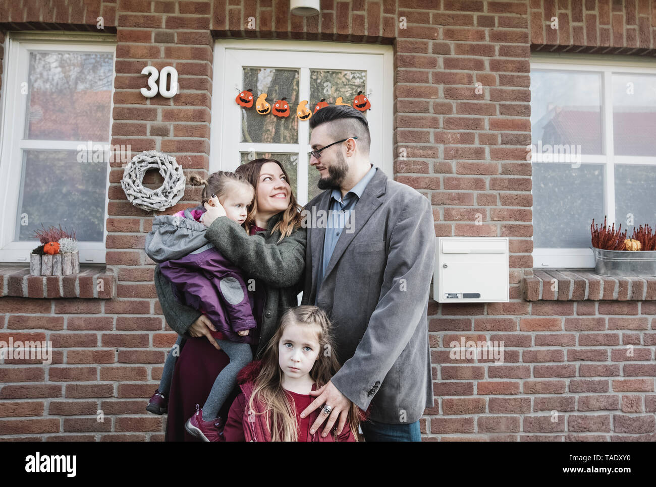 Portrait of family in front of their house - Stock Image
