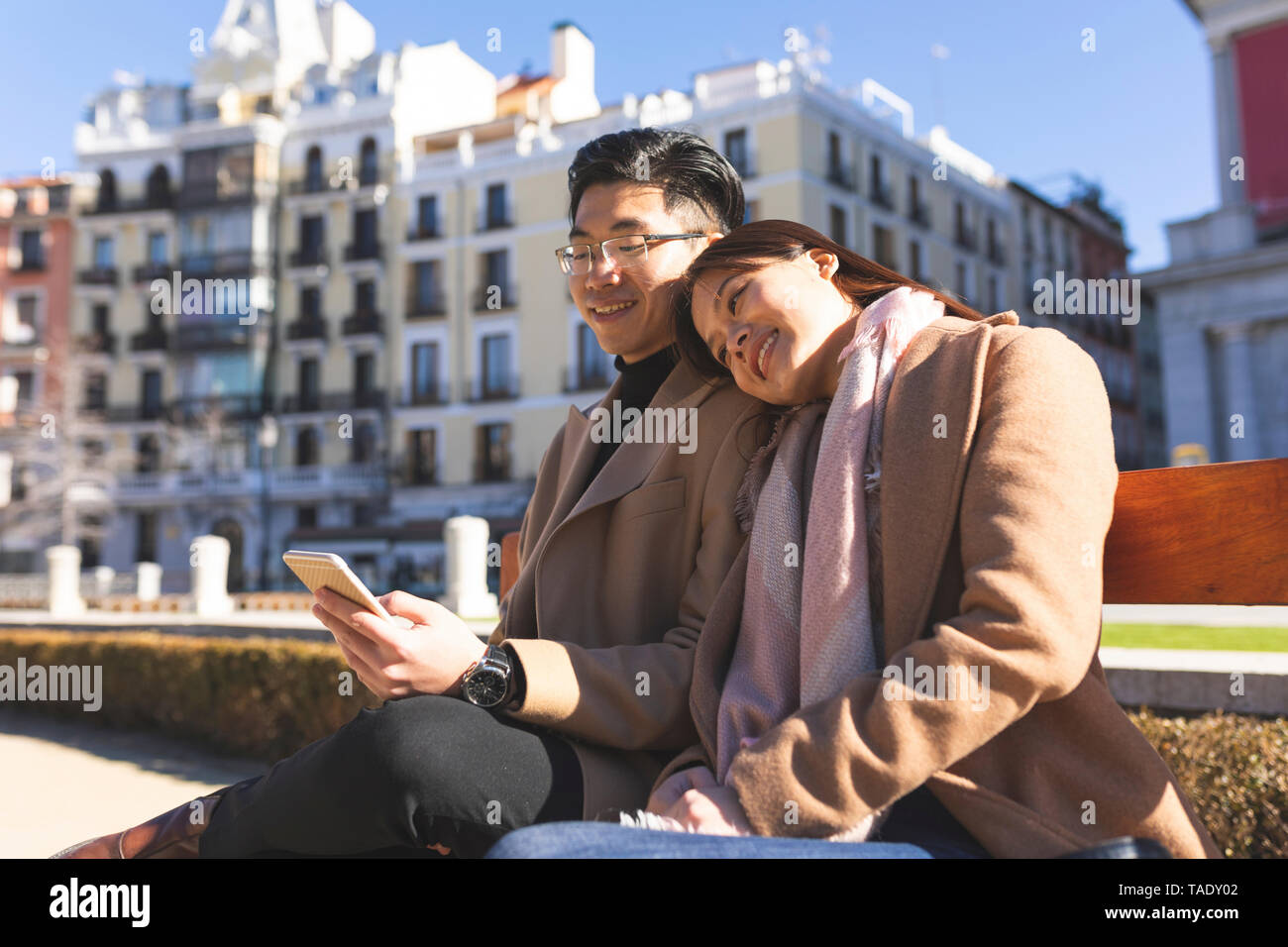 Spain, Madrid, young couple resting on a bench and using cell phone in the city - Stock Image