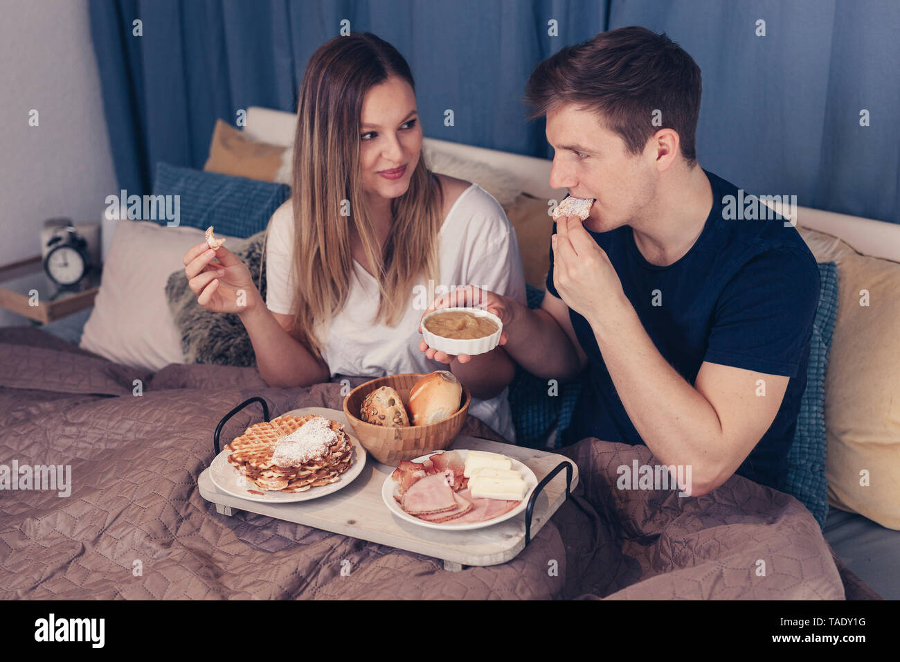 Young couple having breakfast in bed - Stock Image