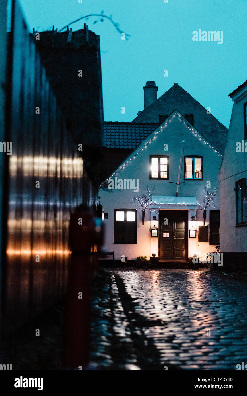 Denmark, Dragor, lighted house in the old town at twilight - Stock Image