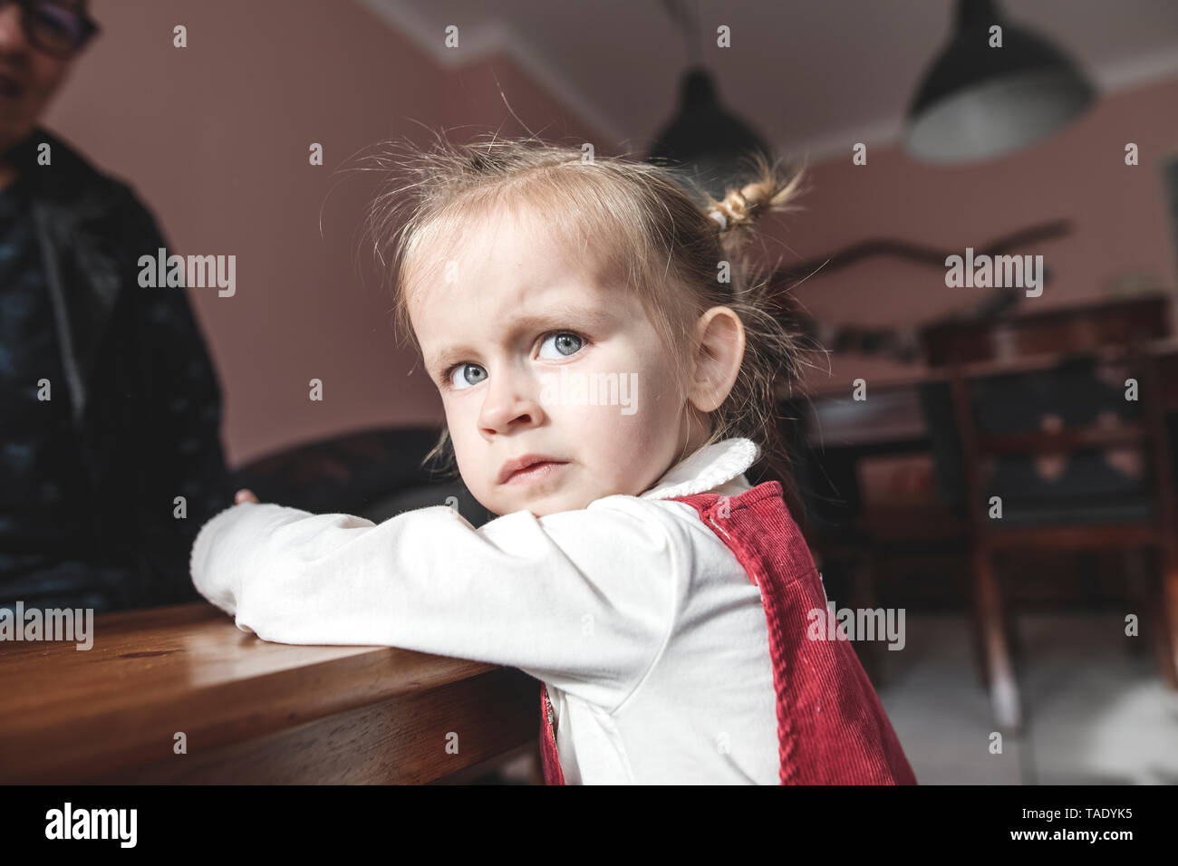 Portrait of girl in living room with grandmother in background Stock Photo