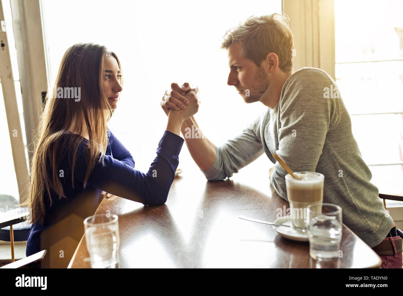 Young couple in a cafe arm wrestling - Stock Image