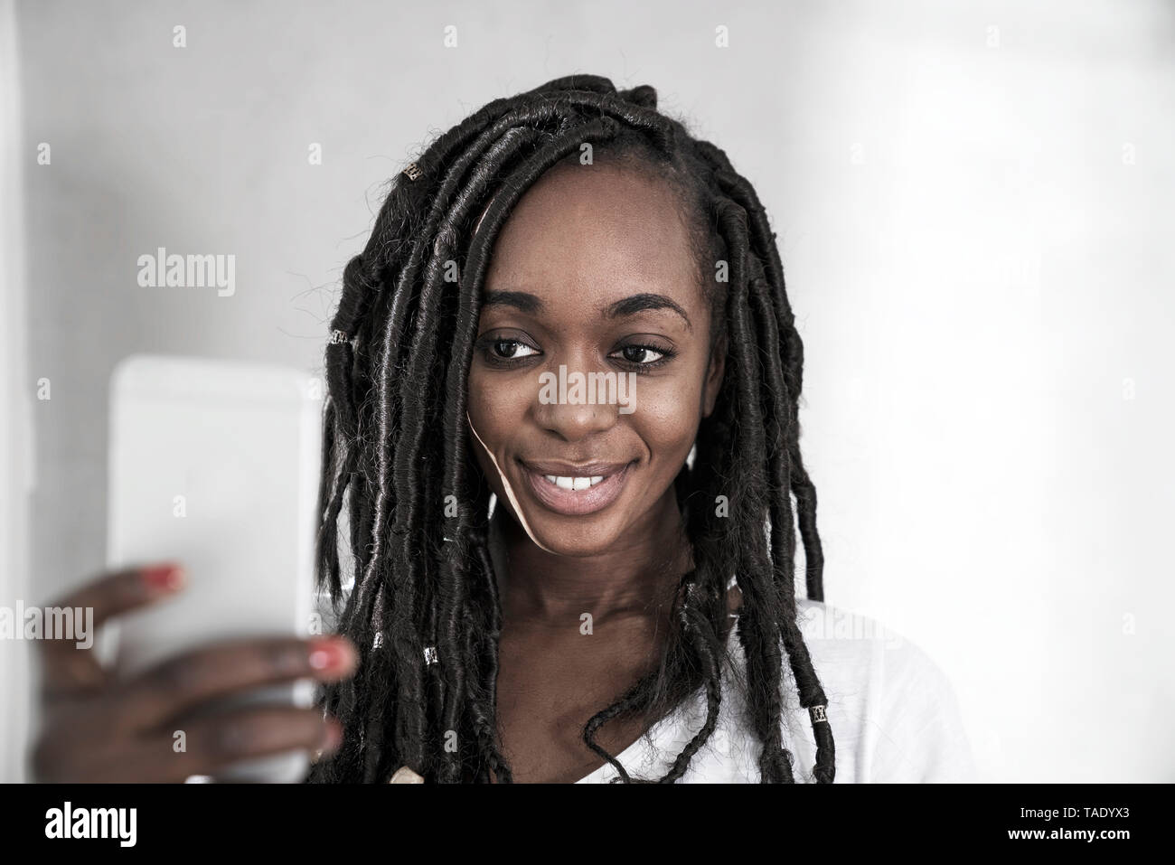 Portrait of smiling woman taking selfie with mobile phone - Stock Image