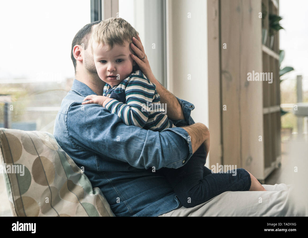 Father cuddling with son at home - Stock Image