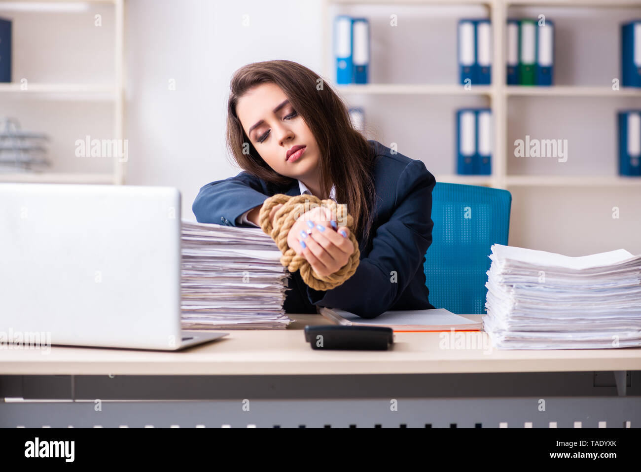 Young beautiful employee tied up with rope in the office - Stock Image