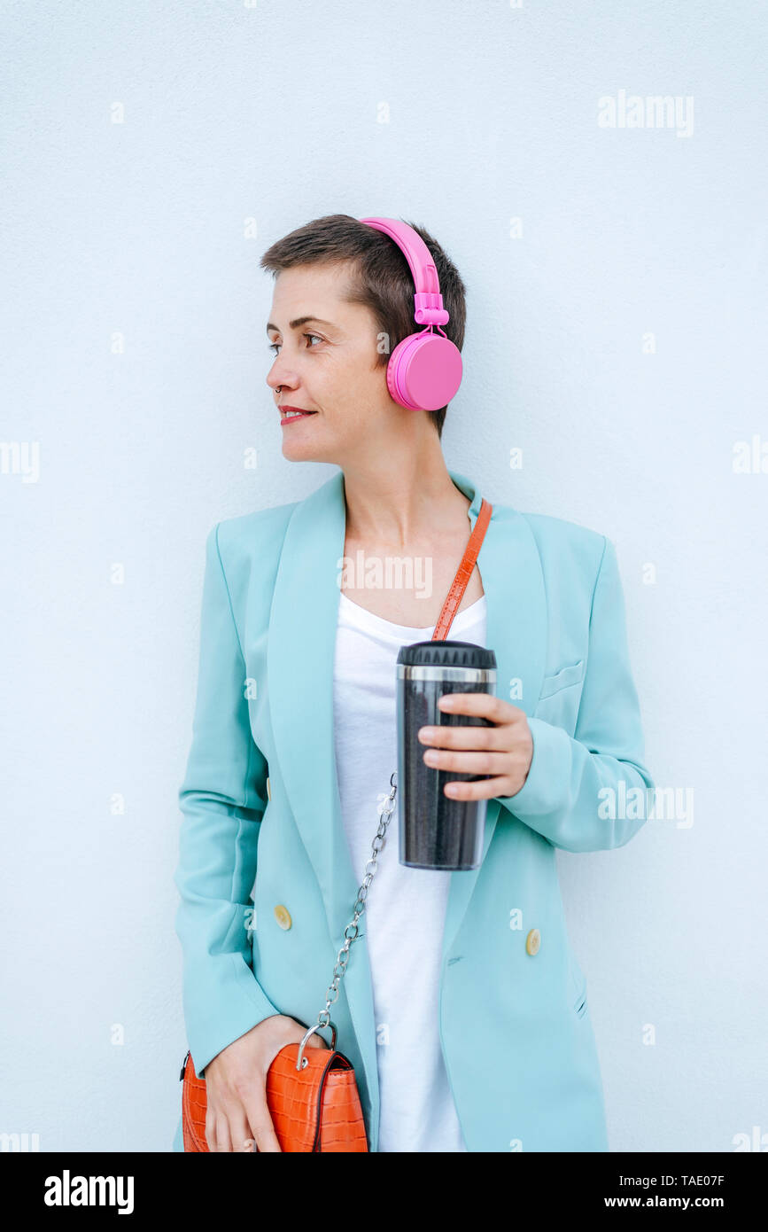 Woman dressed in jacket with thermo mug and pink headphones - Stock Image