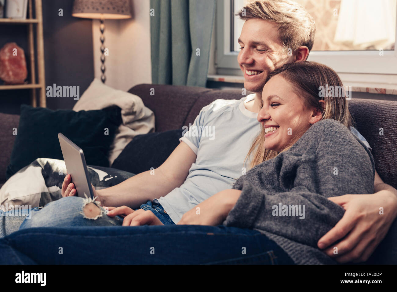 Happy young couple using tablet on couch at home - Stock Image