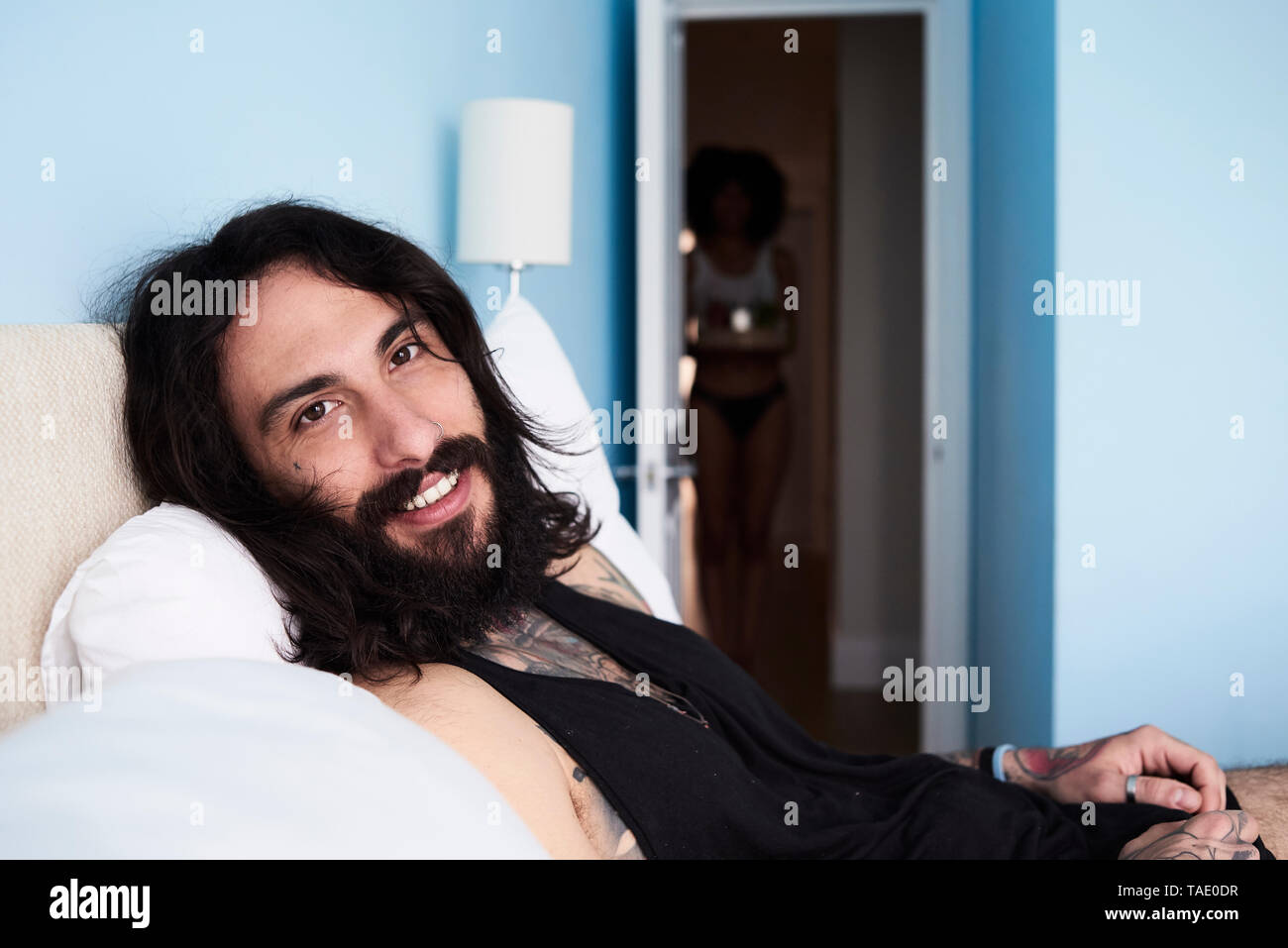 Portrait of smiling tattooed man lying n bed with girlfriend in background - Stock Image