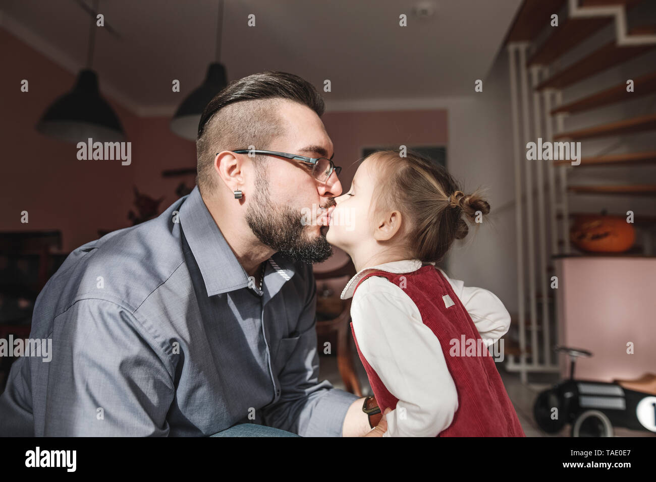 Father kissing daughter in sunshine at home - Stock Image