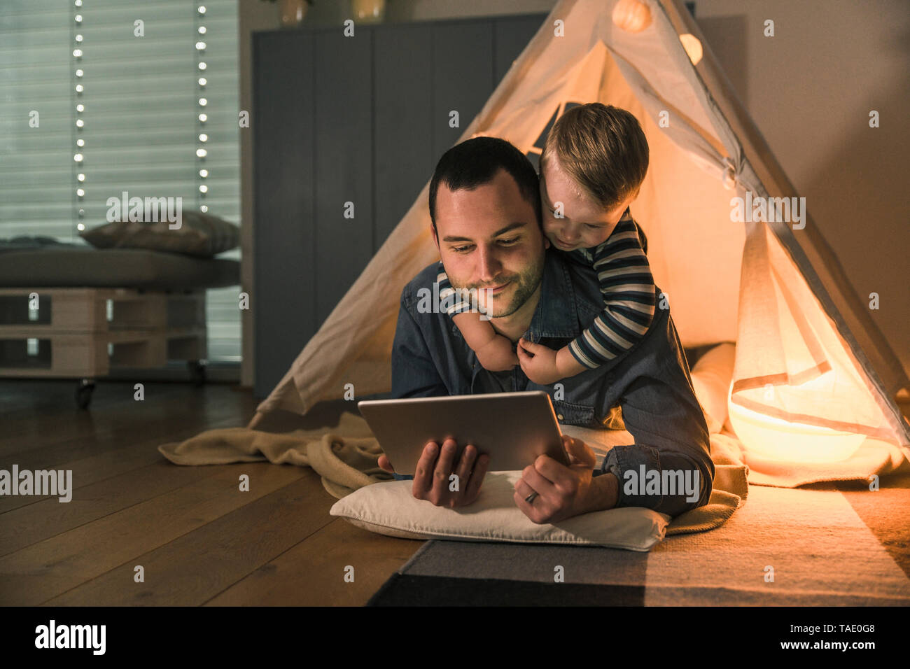 Father and son sharing a tablet at an illuminated tent at home - Stock Image