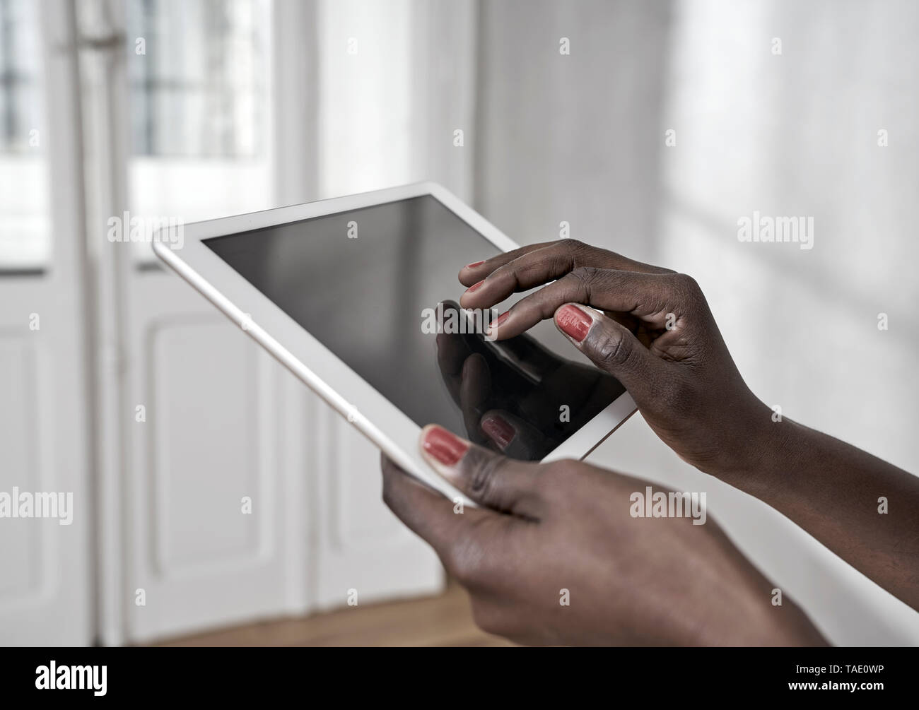 Woman's hands using digital tablet, close-up - Stock Image