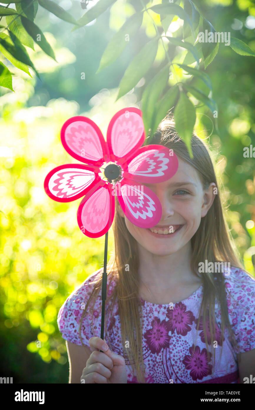 Portrait of laughing girl hiding behind pinwheel - Stock Image