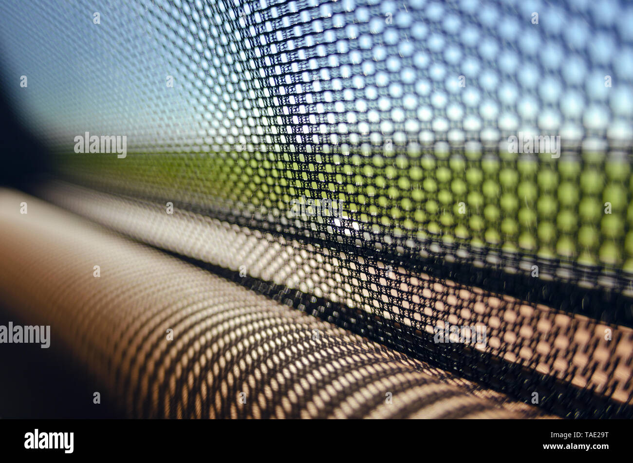 Sun blinds on the glass of the rear door of the car black color close-up protects the textured grid from the sun's rays. Car service. - Stock Image