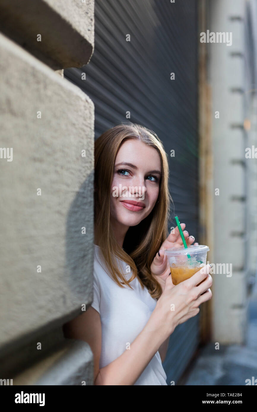 Young woman in the city drinking take-out coffee - Stock Image