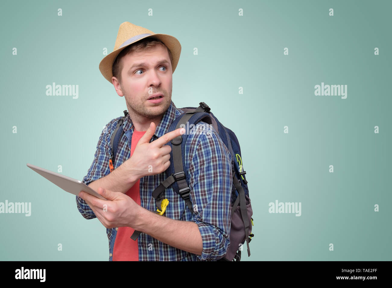 Man lost and looking for direction with tablet - Stock Image