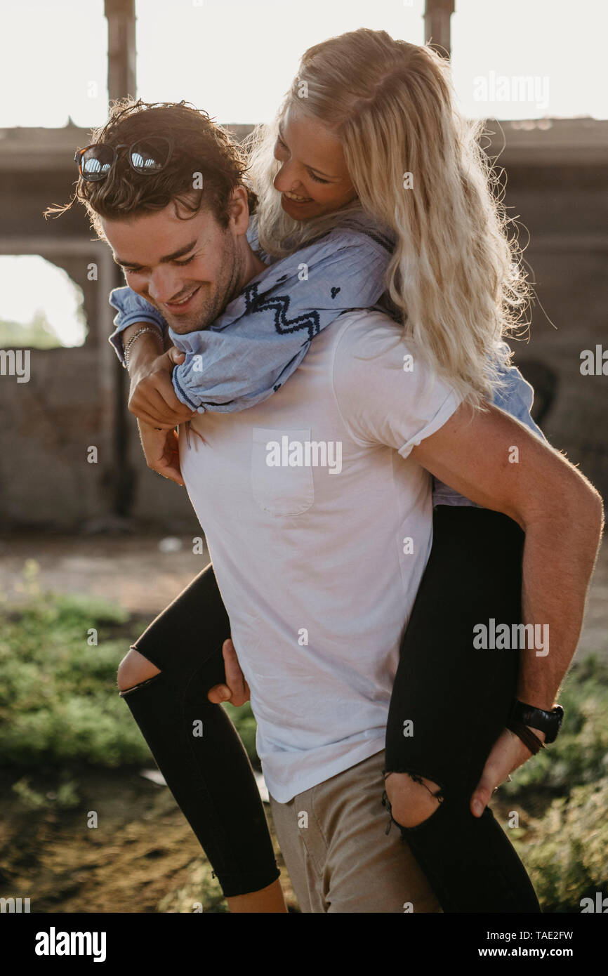 Happy young man giving girlfriend a piggyback ride in an old hall - Stock Image