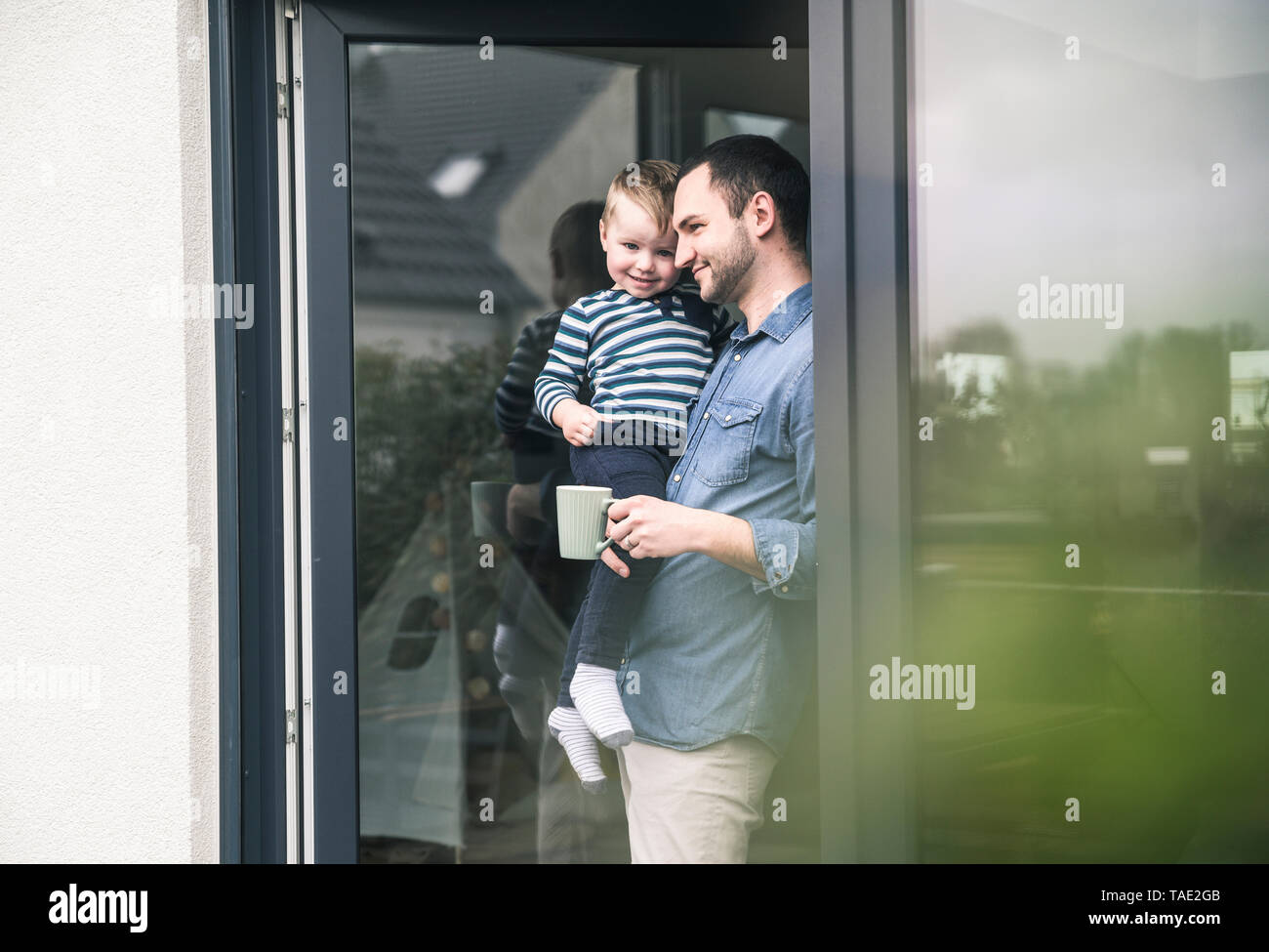 Father with cup of coffee carrying son at terrace door at home - Stock Image