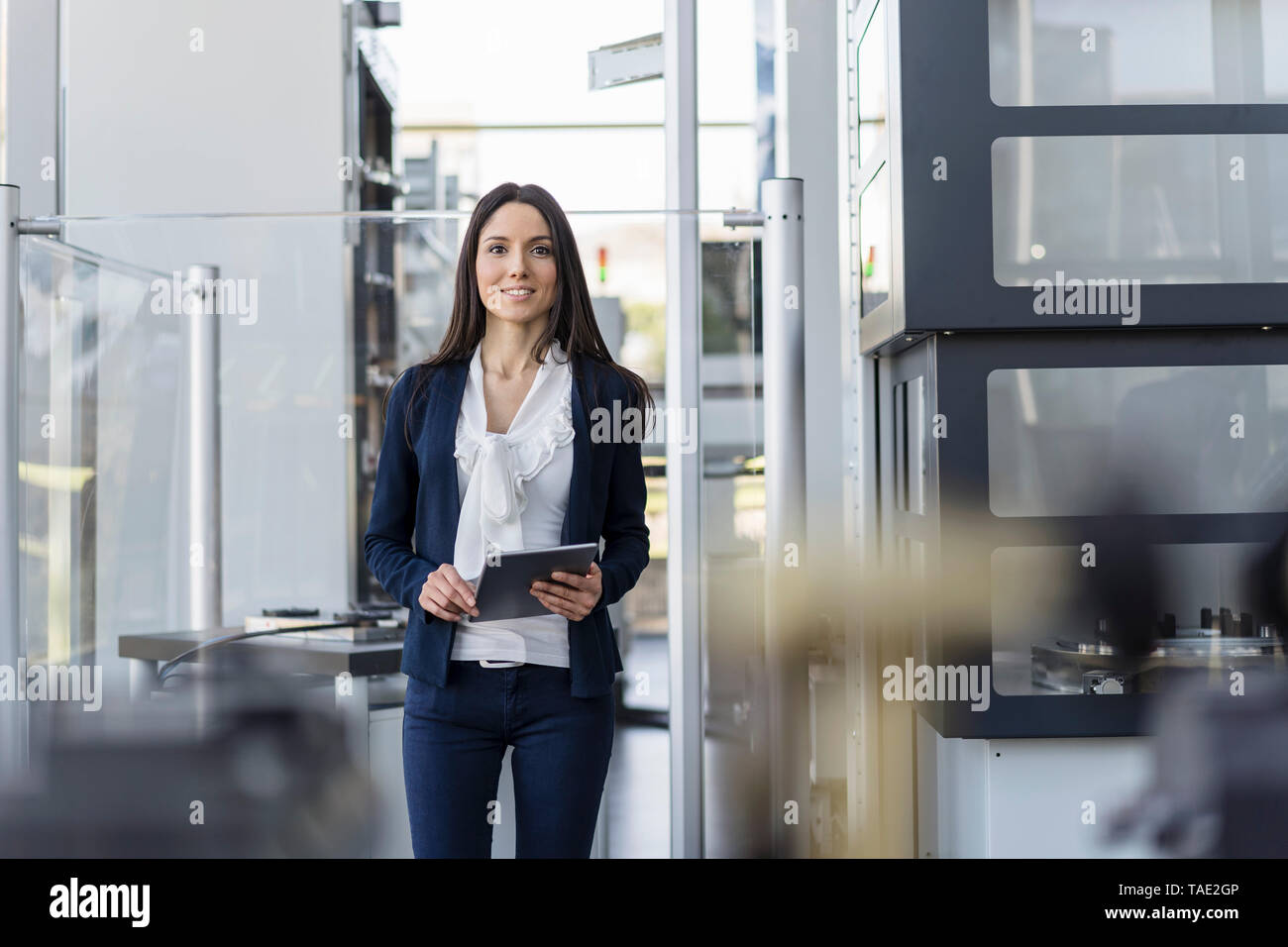 Smiling businesswoman with tablet in a modern factory - Stock Image