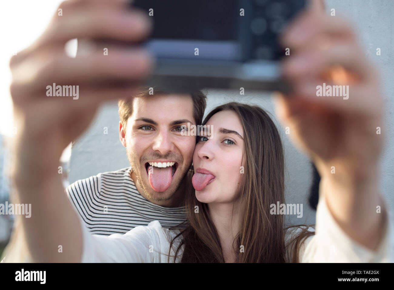 Playful young couple taking a selfie sticking tongues out - Stock Image