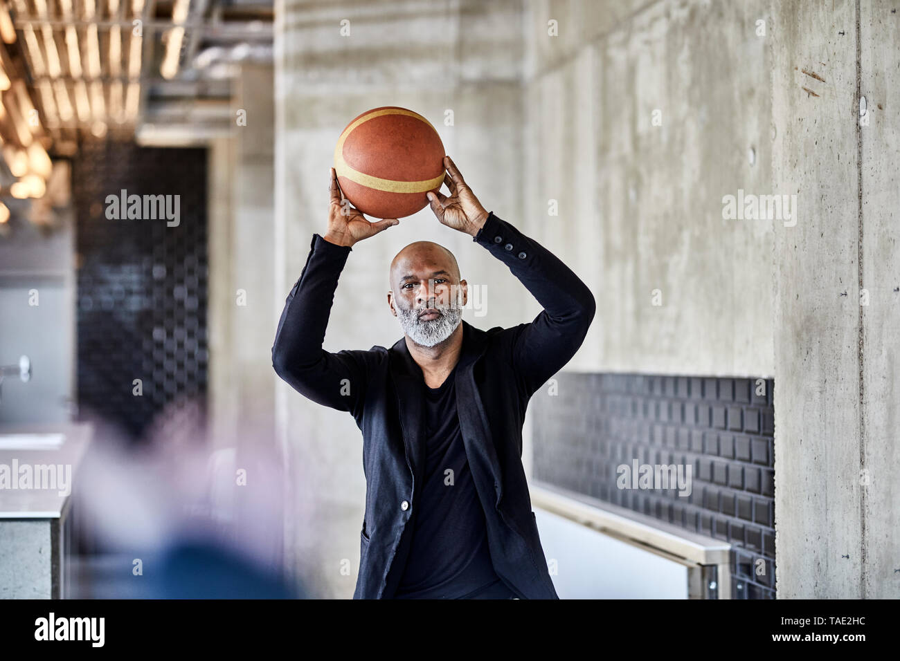 Mature businessman playing basketball in modern office - Stock Image