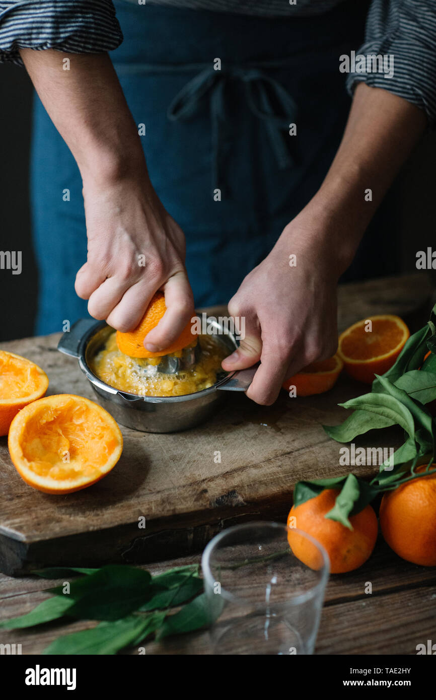 Young man's hands squeezing orange - Stock Image