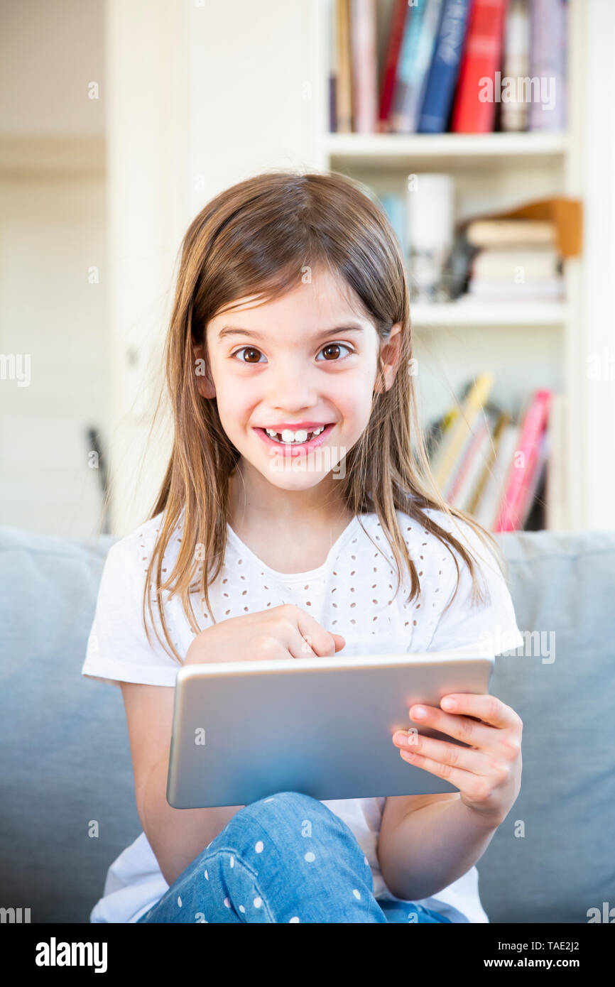 Portrait of happy little girl sitting on the couch at home using digital tablet - Stock Image
