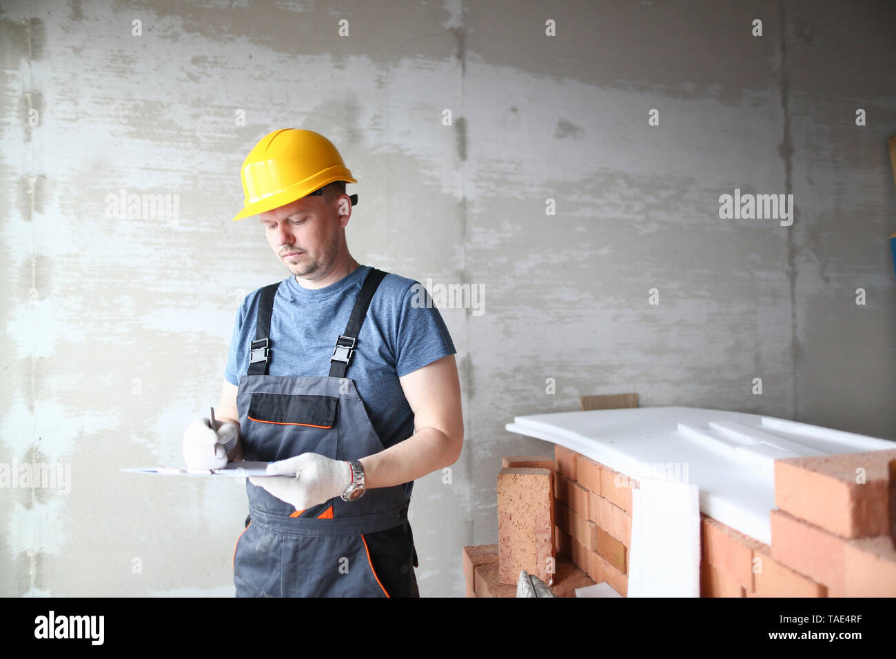 Male builder in yellow hard hat holds - Stock Image