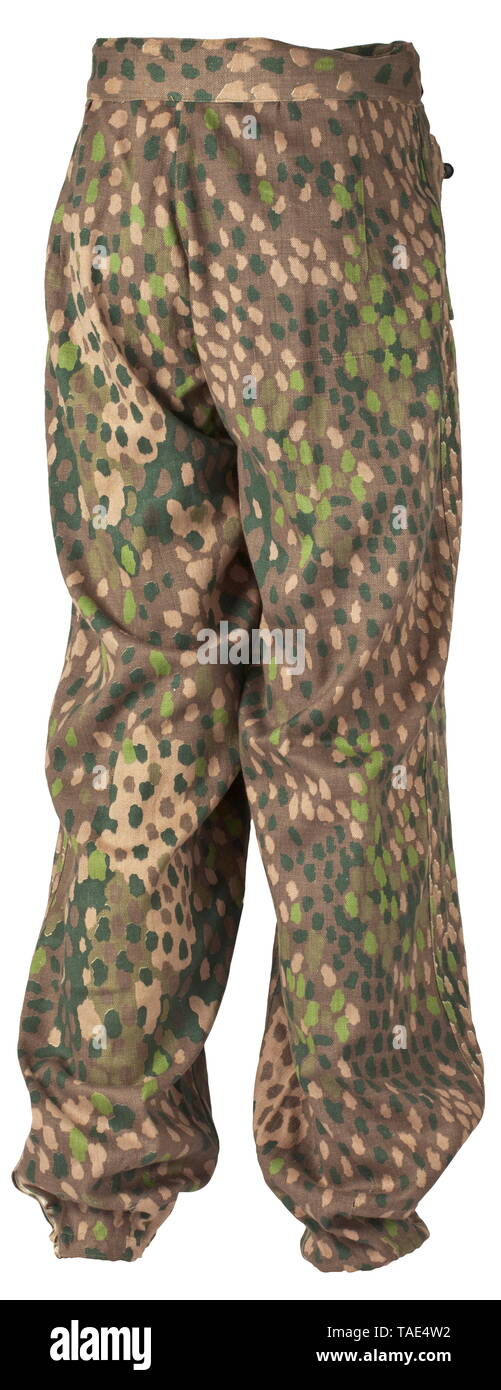 A pair of camouflage trousers M 44 to the special clothing issue for SS Panzer formations depot piece Drill cloth, one side imprinted in pea pattern camouflage with plastic and sheet metal buttons. Rounded waist with sewn in web belt on the right side, on the left a waist extension with buttoned belt closure. Covered fly, integrated fob pocket, both slanted front pockets with closure flaps and a single closure button, wedge-shaped leg terminals with securing strips. The inner liner made from base cloth with size stamping, pocket sacks in white cotton cloth. Very rare trouse, Editorial-Use-Only Stock Photo