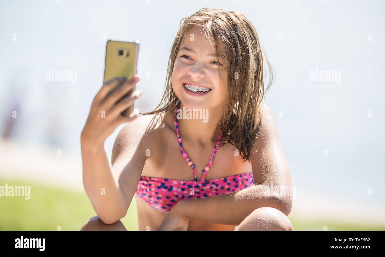 Happy young girl with dental braces making selfhie on beach in summer hot day. - Stock Image