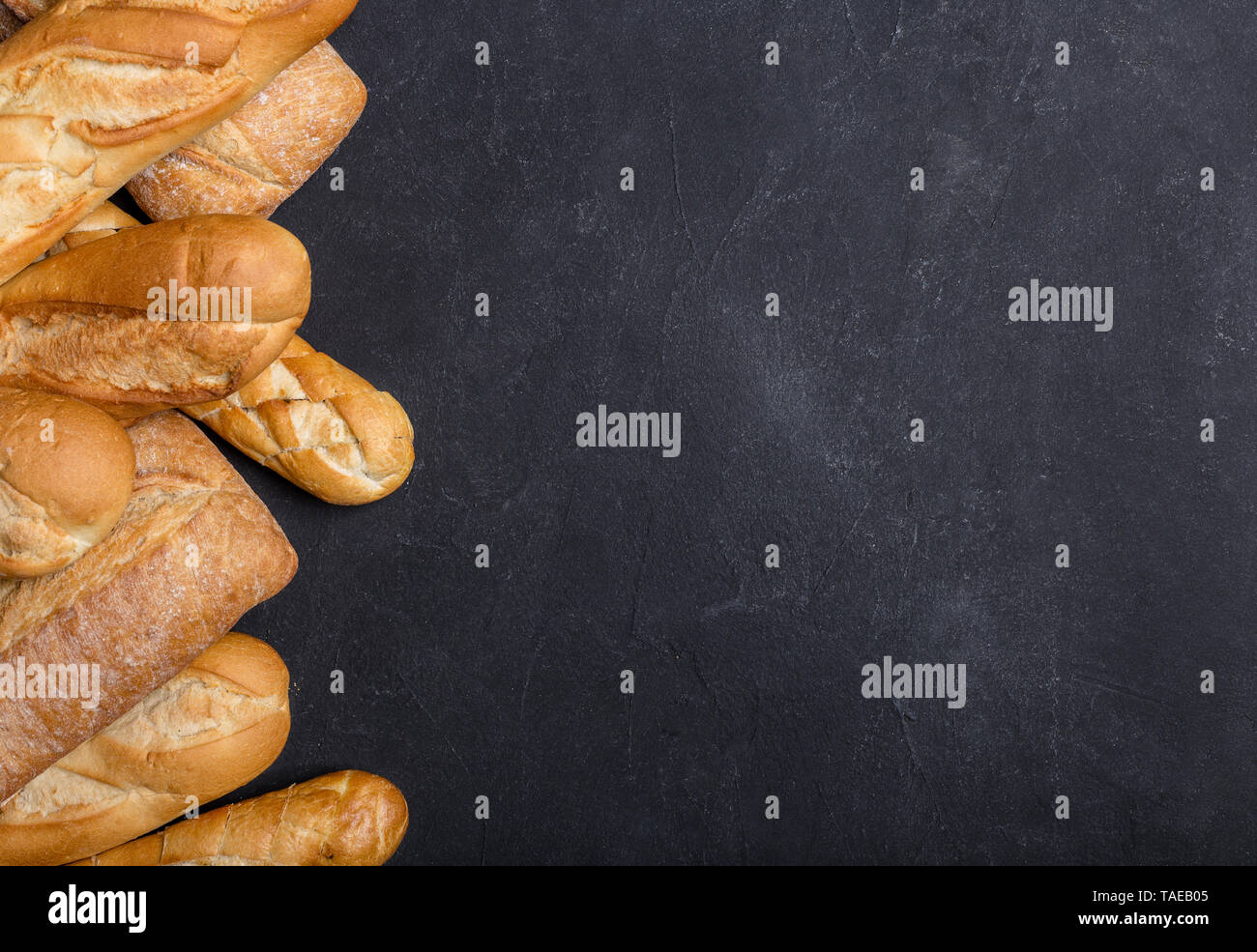 Various crusty bread on black table. Left edge, top view with space for your text. Concept of banner with bread - Stock Image