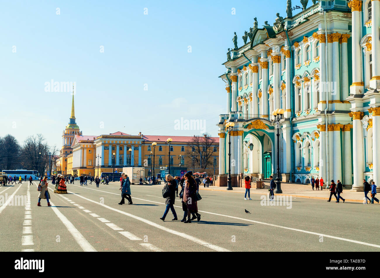 St Petersburg, Russia - April 5, 2019. Tourists walking around the Palace square near the Winter Palace, Hermitage Museum Building. City landscape - Stock Image