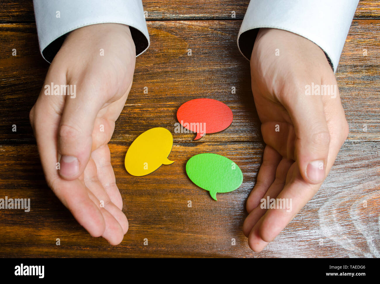 A man collects multicolored speech bubbles in his hands. Listen to other opinions and points of view, accepting criticism and comments. Reverse contac - Stock Image