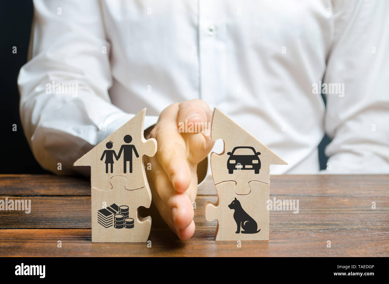 A man shares a house with his palm with images of property, children and pets. Divorce concept, property division process. Marriage contract, custody  - Stock Image