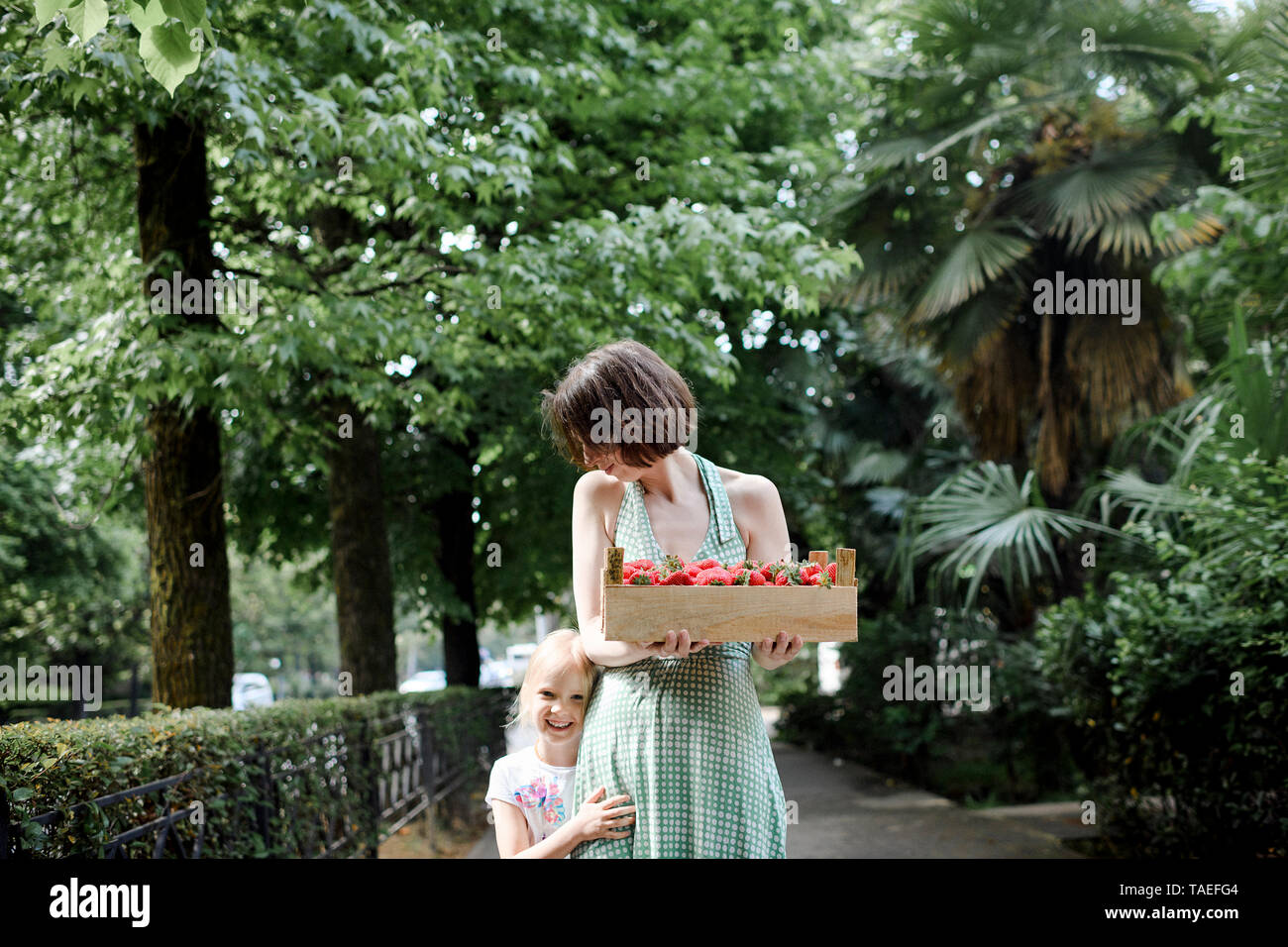 Woman with her daughter holding crate with strawberries - Stock Image