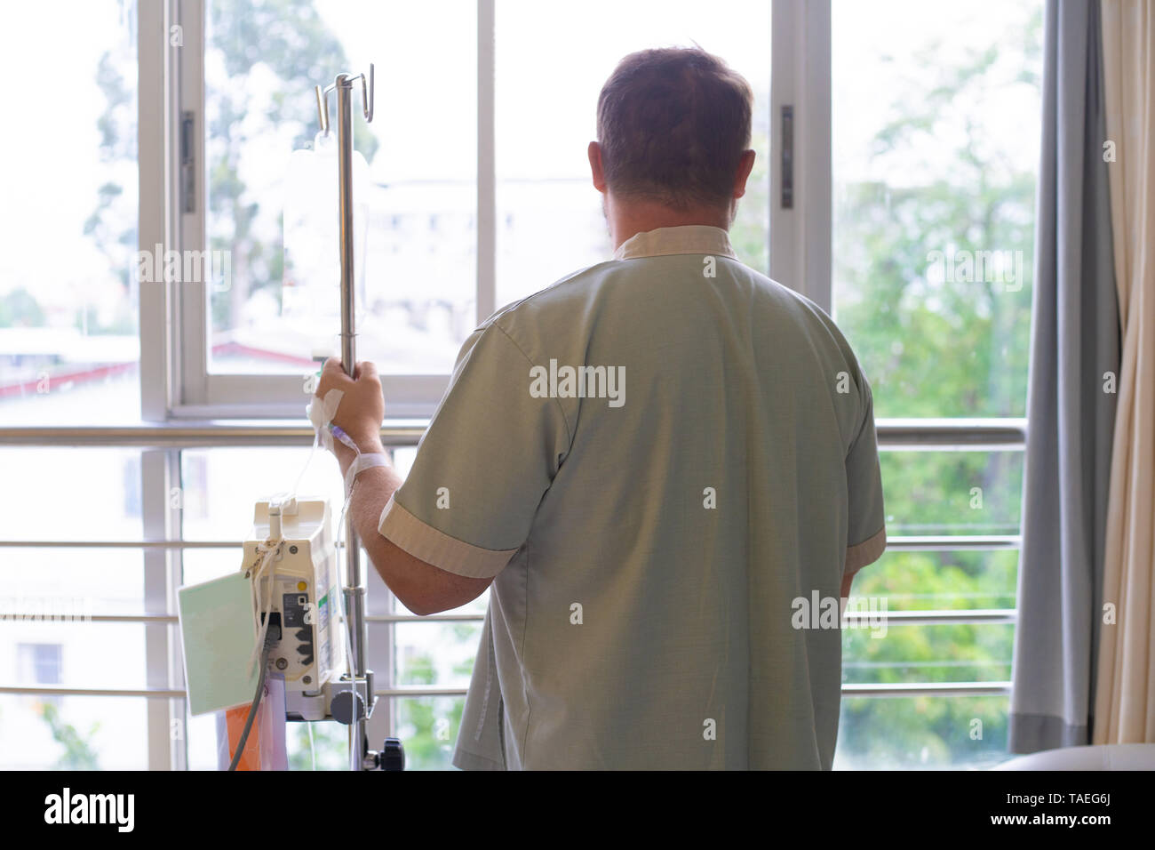 patient with a dropper looks out the window of the hospital room and smiles. back view. Healthcare concept - Stock Image