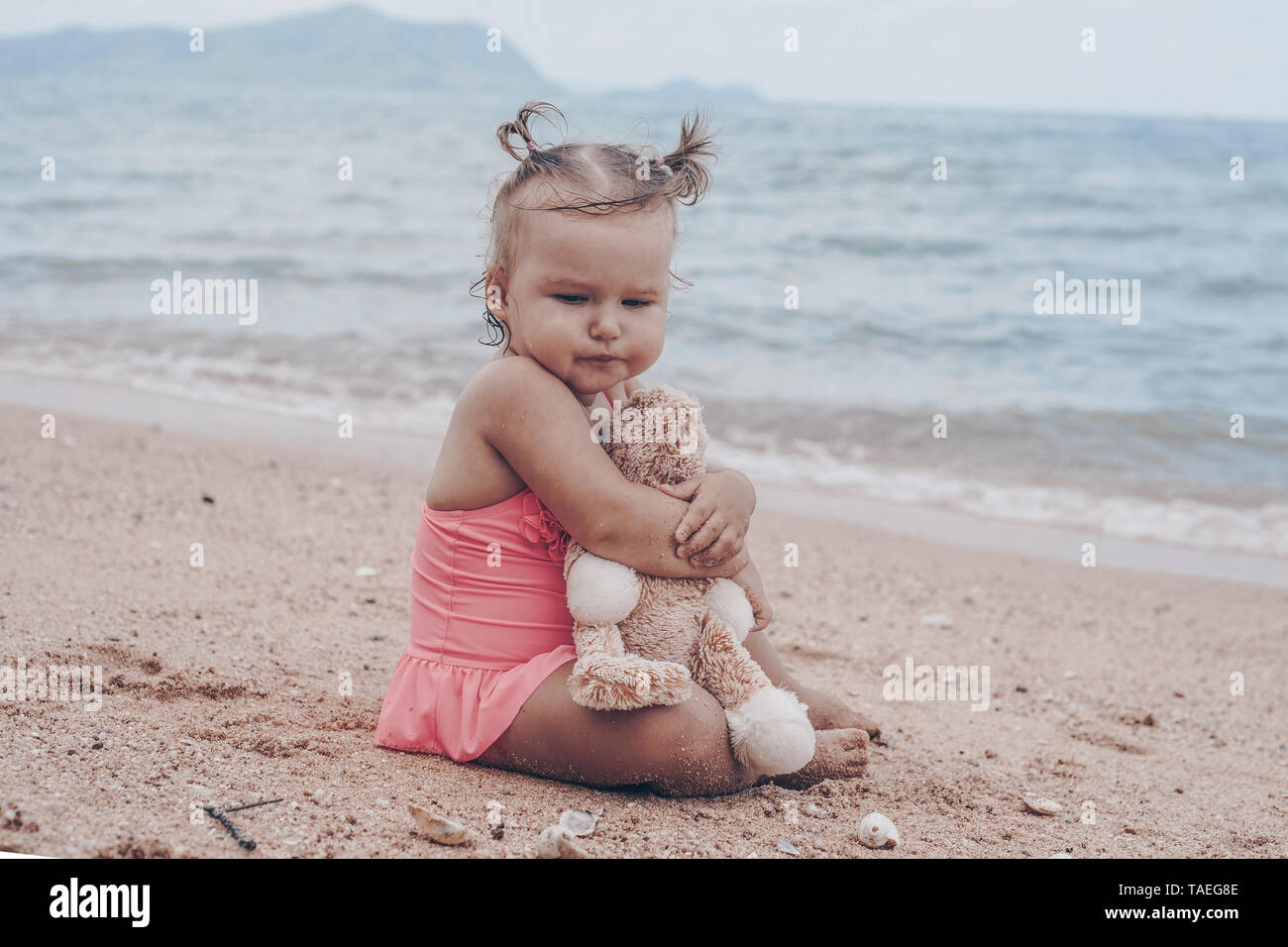 pensive little girl hugging teddy bear and looking away while sitting on seashore. - Stock Image