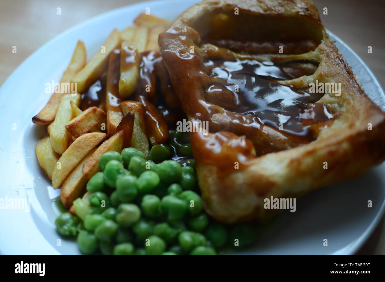 Baked sausages in Yorkshire pudding batter and served with onion gravy, toad in the hole Stock Photo