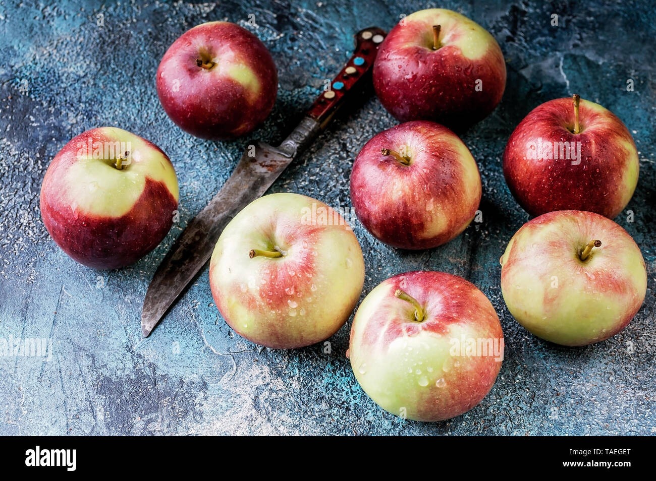 Red apples and knife on dark blue concrete background. Autumn harvest - Stock Image