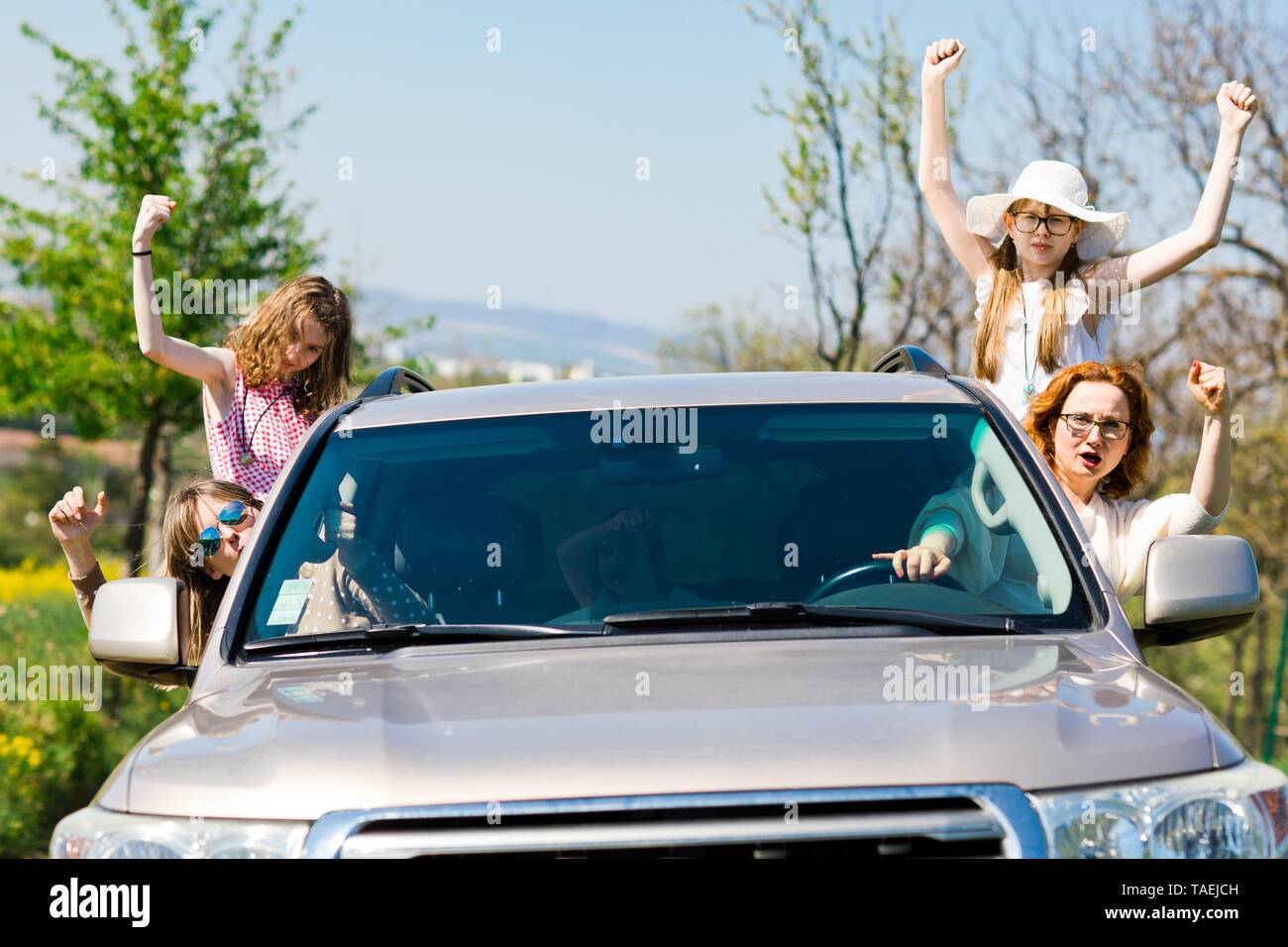 Female rioters behind the wheel, hooligans in the car showing gestures all around Stock Photo