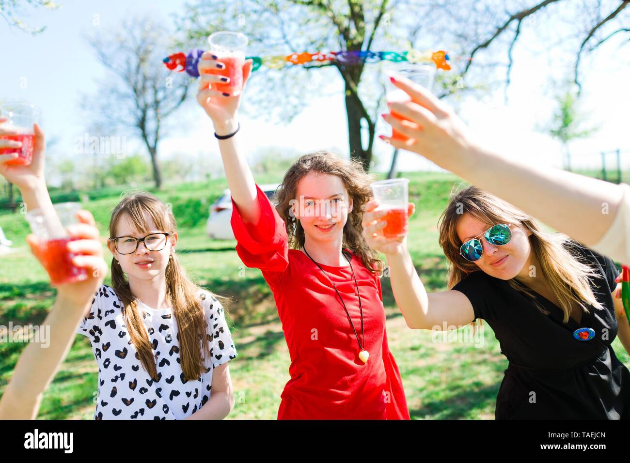 Toast with child champagne on birthday garden party using plastic cups - Stock Image