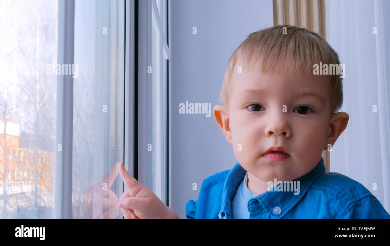 Pensive little boy looking at camera - Stock Image