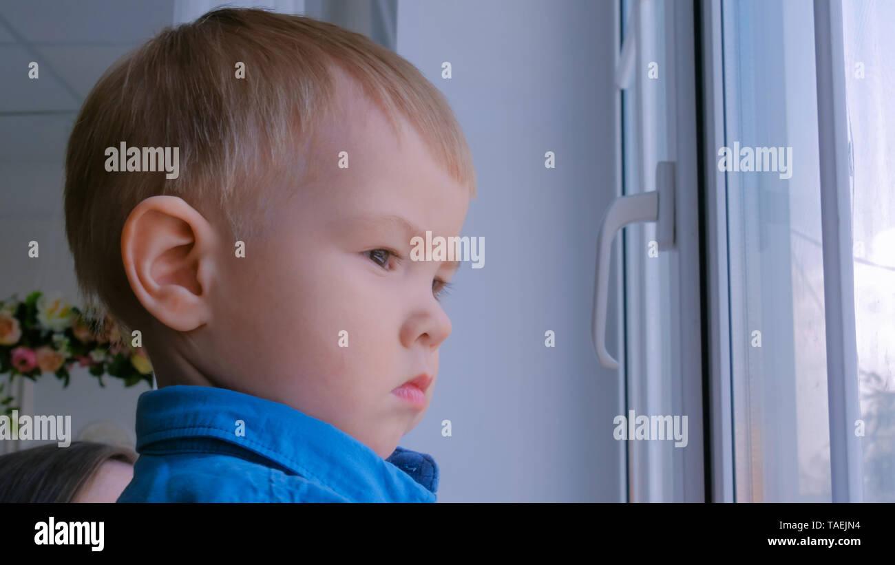 Pensive little boy looking through window - Stock Image