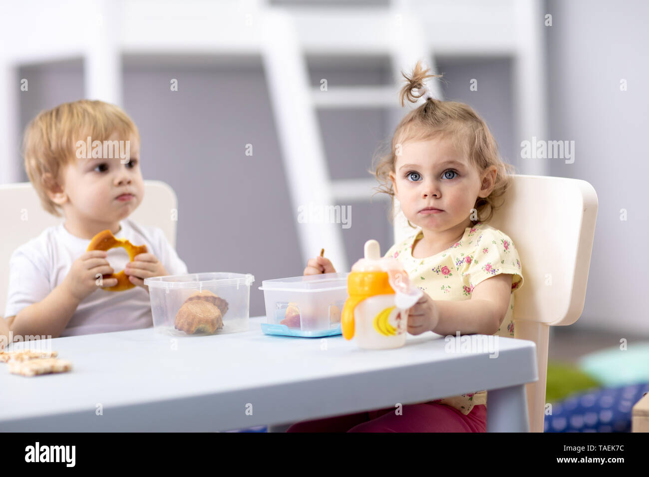 Time to eat in kindergarten. Babies have a lunch in day care center - Stock Image