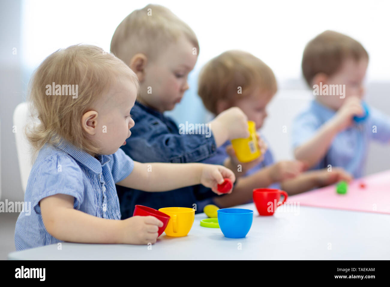 babies group learning arts and crafts in playroom with interest - Stock Image
