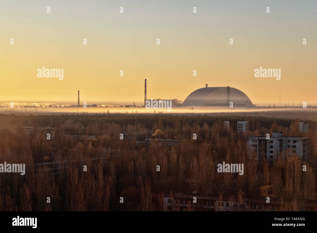 Cityscape view of Pripyat, Ukraine, inside the Chernobyl Exclusion Zone, with the Chernobyl Reactor in the background Stock Photo